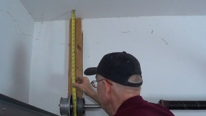 A professional using a tape measure to determine the distance between the ceiling and the top of the cable drum.