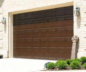 An image of a brown panel garage door on a brick house.