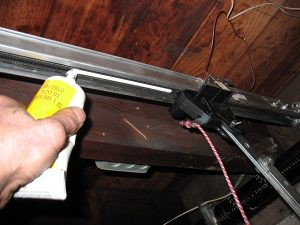 An image of a hand lubricating a Genie screw drive opener to prevent garage door noise.
