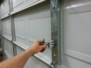 A person aligning a garage door lock into the center stile holes.
