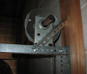 An angle that is bolted to the horizontal angle and wedges against the jamb to support the end bearing plate.