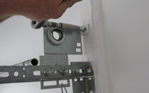 A person shown securing the top of an anchor bracket with a lag screw on a 15-inch radius track.