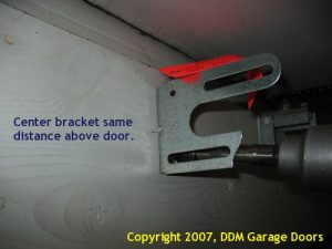 A person screwing in a spring anchor bracket to the header.