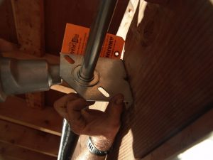 An image of a spring anchor bracket mounted on a torsion spring shaft.