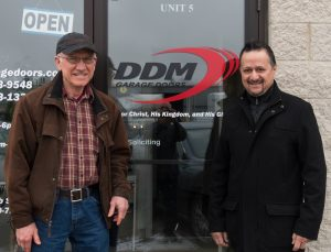 A picture of Dan Musick standing  with Ray Bansal outside of DDM Garage Doors office.