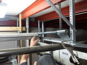 A garage door professional installing a spring bumper on a horizontal track using a c-clamp.