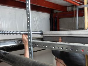 The garage door is being raised and the spring bumper is aligned.