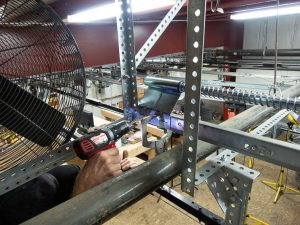 A man drilling holes in the horizontal track using a 3/8 inch drill bit.