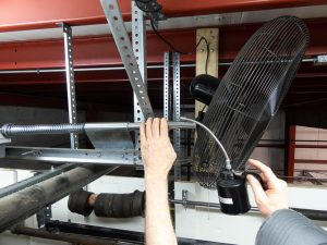 A garage door professional with an oil can in his hand shown lubricating the rod of the spring bumper.