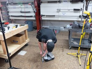A garage door professional testing the compression on a 27-inch spring bumper by using an analog scale.