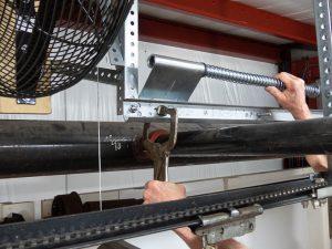 A garage door professional adjusting the spring bumper bracket using a c-clamp.