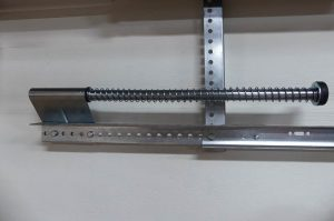 A horizontal garage door track with a 2-inch angle added to the inside of the track.