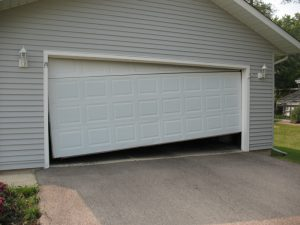 A white crooked garage door with the right side of the door lifted off the ground.