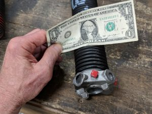 An image of a hand trying to place a one-dollar bill in between standard torsion spring coils. However, the bill does not fit in between the coils.