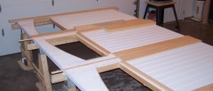 White custom garage doors laying on sawhorses awaiting assembly.