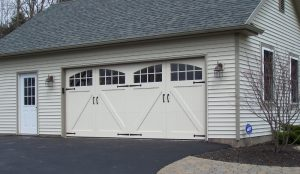 An almond colored house with custom garage doors containing windows.