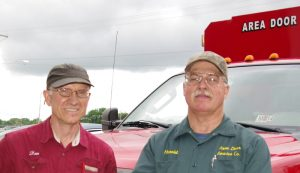 "Picture of Harold Poling (on the right ) and Dan Musick (on the left) in front of an ""Area Door Service Co."" red truck."