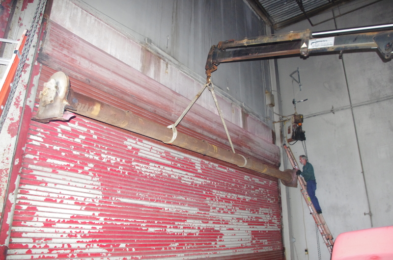 A view of the barrel of a steel rolling door being supported by a crane in order to replace steel rolling door springs.