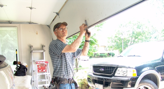 A Garage Door Service Professional standing with the garage door opened and looking at the door to diagnose the issue.