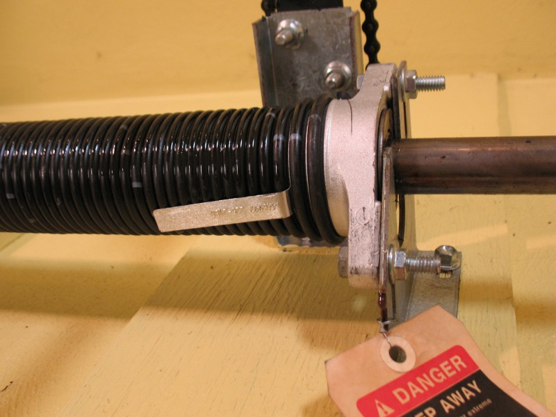 Image showing Raynor torsion spring with a metal tag identifying it
