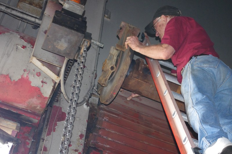 A man standing on a ladder removing an endplate to replace the steel rolling door spring.