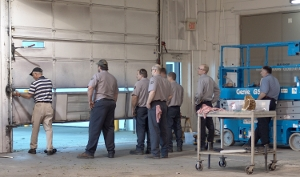 Dan Musick is training maintenance personnel to replace a bottom garage door section.