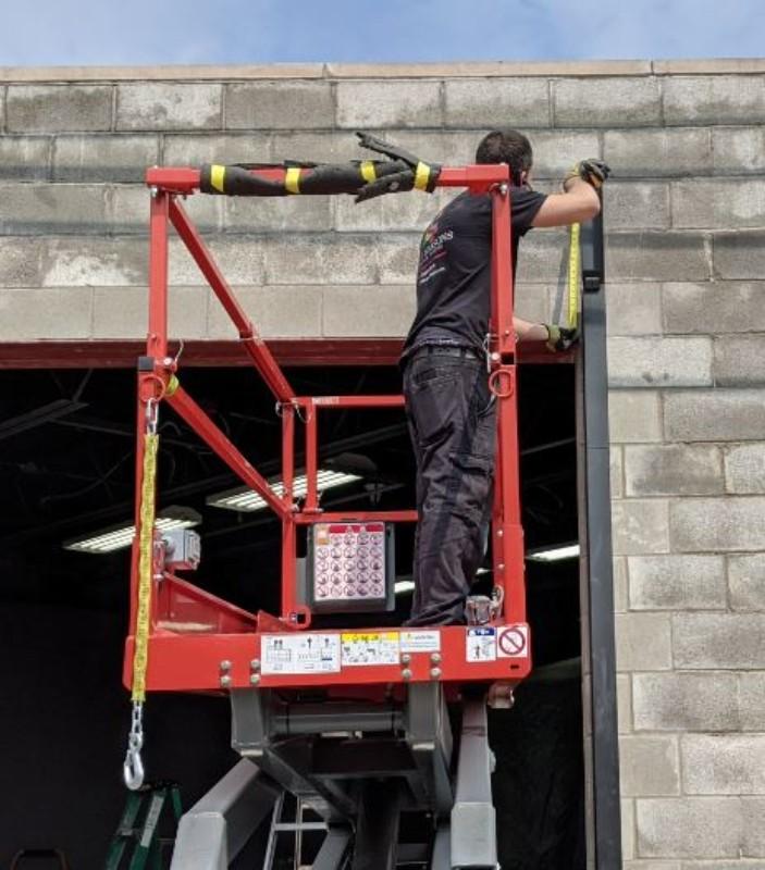 A garage door installer is measuring both sides from the level steel header.