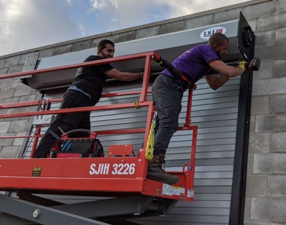 Two installers standing on a scissor lift skyjack securing a curtain door hood.