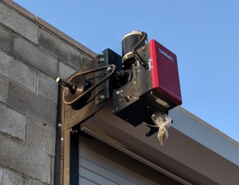 An image showing a Commercial Door Operator installed on a steel rolling door.