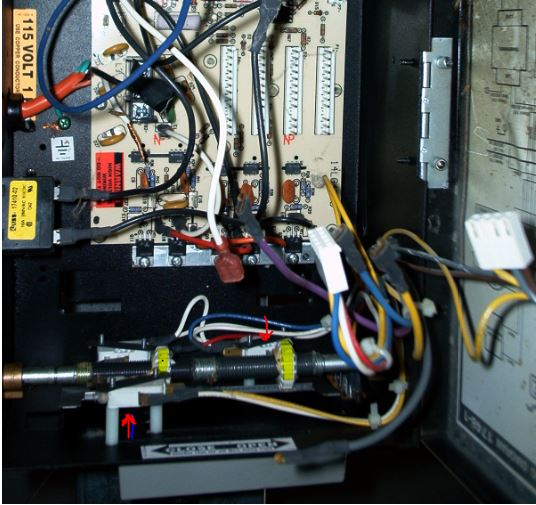 An image of the inside of a LiftMaster operator showing the limit nuts and switches.
