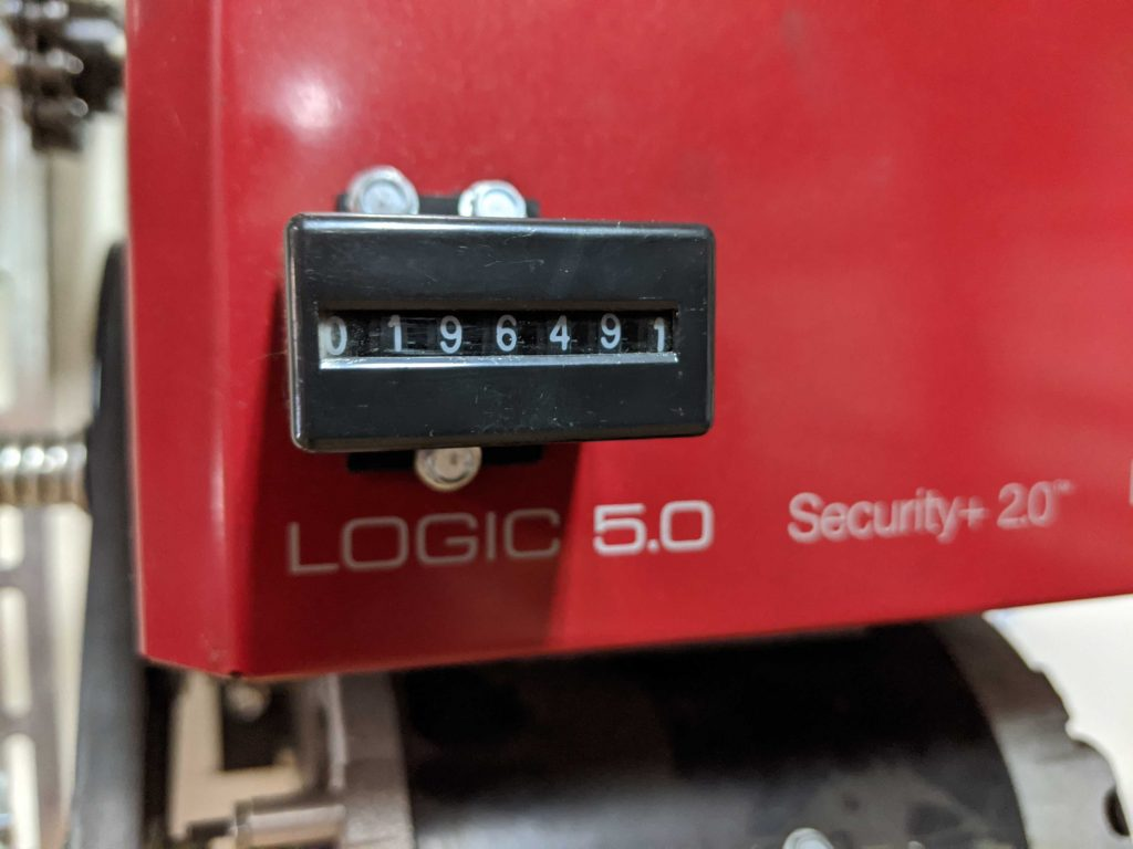 An image of  a LiftMaster operator with an external counter showing 196,491 cycles.