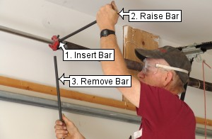 Insert second bar to unwind garage door torsion springs.