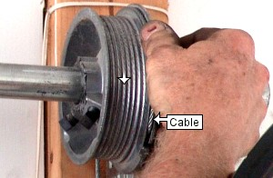Tighten garage door cable on drum.