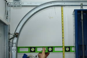 the horizontal and vertical track holding it level and measuring the distance between the bottom of the the horizontal track and the level as shown - Garage Door Vertical Track