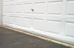 Bent garage door. Damaged from fall with broken spring