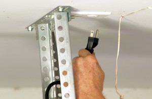 Unplug power to garage door opener to safely replace torsion springs.