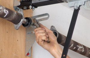 Secure garage door shaft to spring anchor bracket.