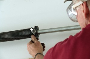 Check winds of garage door torsion springs.